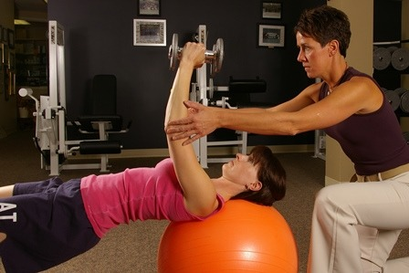 Physiotherapist assisting woman on yoga ball with weights