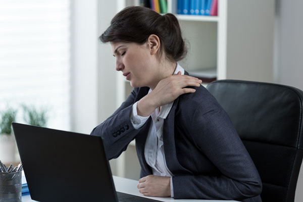 Colour photo of woman at computer with shoulder pain