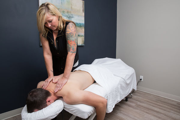 Massage therapist treating male patient
